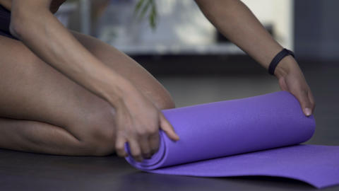 Fit girl kneeling on floor and rolling out yoga mat, leisure time, active hobby Footage