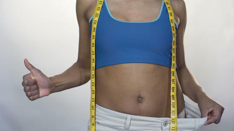 Fit woman pulling waist of oversized pants away, showing thumbs-up, weight loss Footage