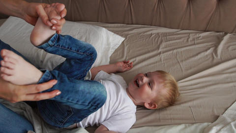 Mom and father tickling her child. people, family, fun and morning concept - Footage