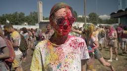 Young happy girl in colors is thrown with colourful powder on holi festival in Footage