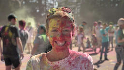 Young happy girl in colourful powder is smiling on holi festival in daytime in Footage
