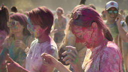 Three young happy multi-ethnic girlfriends are dancing on holi festival in Footage