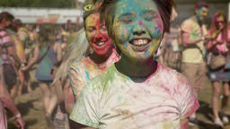 Three young happy multi-ethnic girlfriends are jumping in conga line on holi Footage