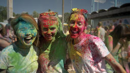 Three young multi-ethnic girlfriends are laughing on holi festival in daytime in Footage