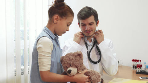 The good doctor is listening through a stethoscope girl s soft toy Footage