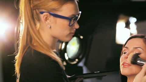 makeup artist prepares woman presenter to show GIF