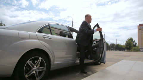man in suit helps director get out of car at office GIF