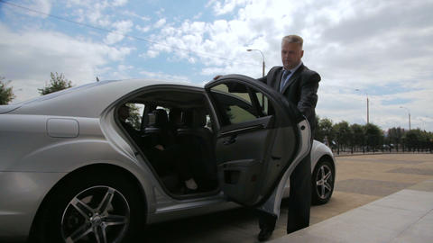 man in office suit opens car door and business man gets out Footage