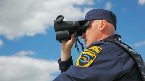 water patrol officer with binoculars sails on boat Footage