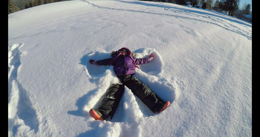 Kid making snow angels in snow during winter 4k Footage