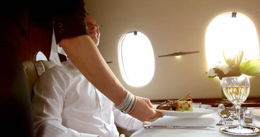 Flight attendant serving meal to businessman 4k Footage