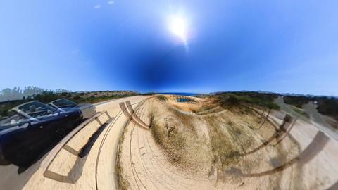 automobile drives along sand cliff against ocean seascape Footage