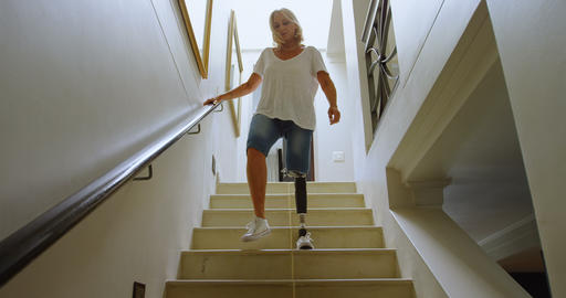 Disabled woman with prosthetic leg moving downstairs 4k Footage