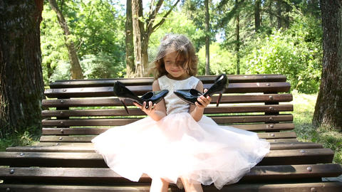 Little girl on the bench holding big shoes Footage