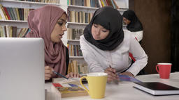 Young muslim female students in hijab studying in library, preparing for exam Footage