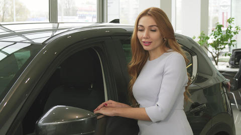 Happy young attractive woman showing thumbs up posing near a new car at the Footage