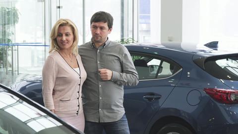 Mature couple choosing a new automobile at the dealership salon Live Action
