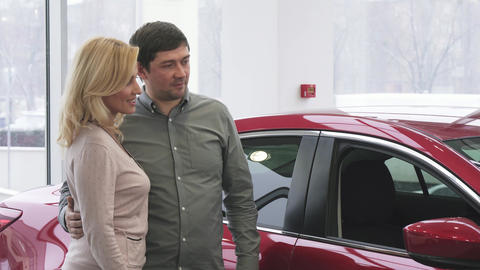 Cheerful mature couple buying a new car at the dealership showroom Footage