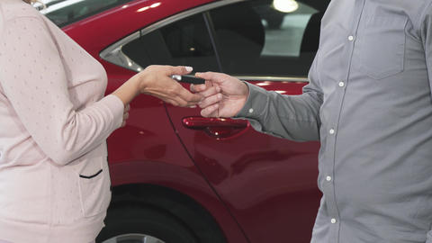 Cropped shot of a woman receiving keys to her new auto at the dealership Footage