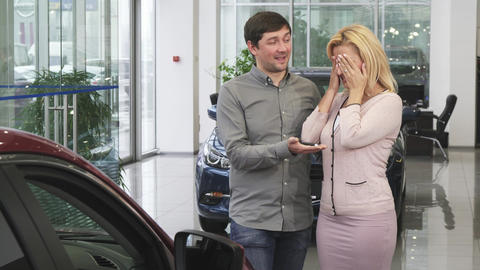 Mature man buying a new car for his gorgeous wife at the dealership salon Footage