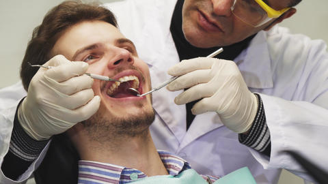 Handsome young man smiling during dental examination Footage