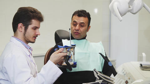 Professional dentist showing dental mold to his mature patient Footage