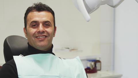 Happy mature man smiling holding an apple sitting in a dental chair Footage