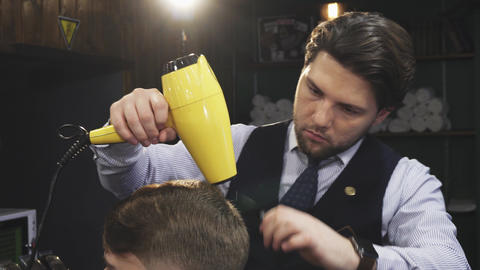 Professional barber blow drying hair of his client Footage