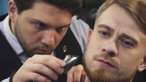 Close up of a professional barber trimming beard of a young man Footage
