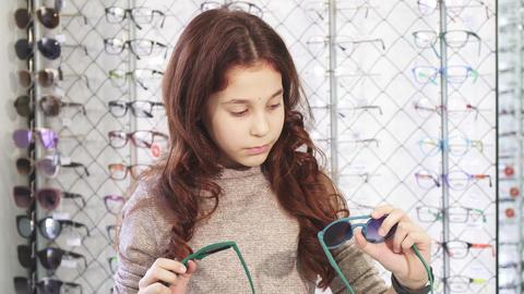 Pretty little girl looking confused choosing between two pairs of sunglasses Footage
