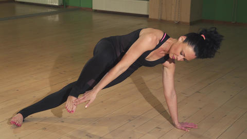 Beautiful woman doing yoga indoors stretching her body elegantly Footage