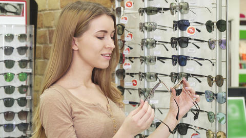 Young happy beautiful woman choosing between two pairs of sunglasses Footage