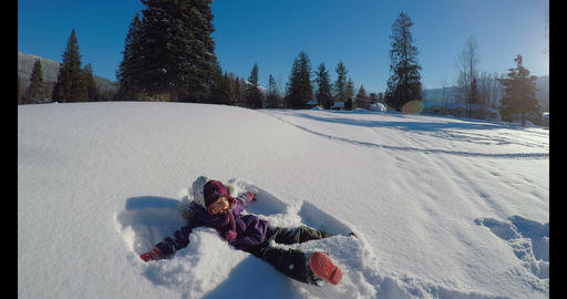 Kid making snow angels in snow during winter 4k Live Action