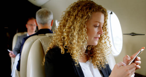 Businesswoman using mobile phone in private jet 4k Live Action
