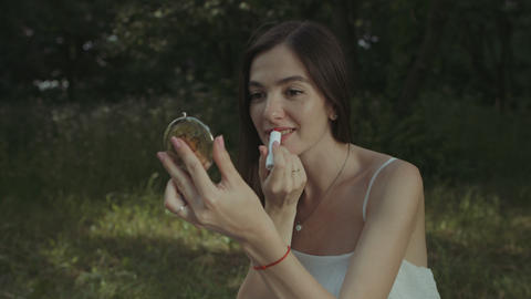 Charming woman applying lipstick in park GIF