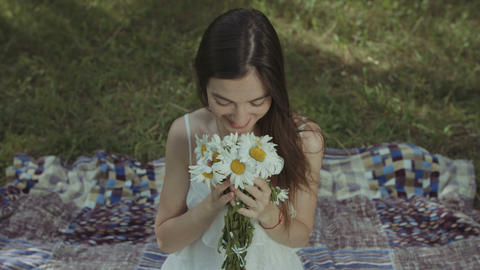 Pretty smiling woman smelling chamomiles in park GIF