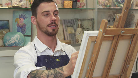 Handsome bearded male artist working on a painting at his Art Studio Footage