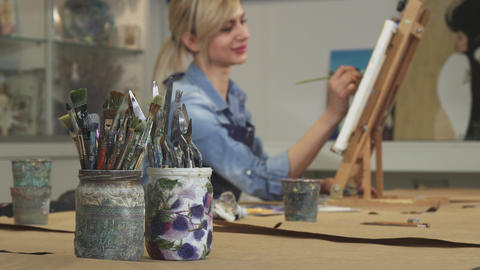 Selective focus on a bunch of paintbrushes female artist working on her painting ライブ動画