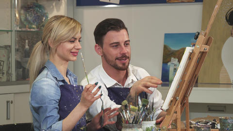 Happy couple painting a picture together on a date at Art Studio Footage