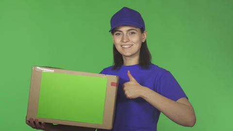 Attractive young delivery woman showing thumbs up holding cardboard box Footage