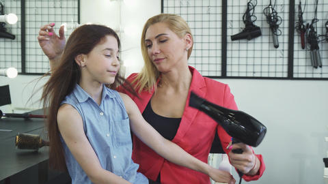 Beautiful woman drying hair of her daughter with a hairdryer at the beauty salon Footage