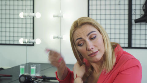 Mature woman looking upset examining her hair with split ends Footage