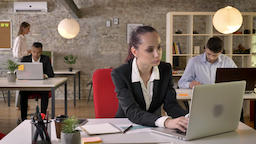Young beautiful business woman is watching laptop in office, watching at camera Footage
