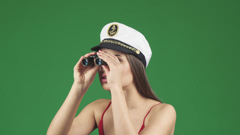Sexy young woman in a sailor cap looking away with binoculars smiling joyfully Footage