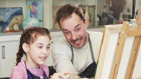 Happy little girl painting a picture with her father Footage