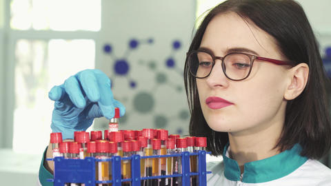 Young female researcher examining test tubes with blood samples Footage