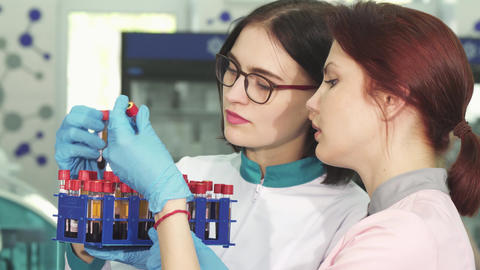 Two young female researchers working with blood test tubes Footage