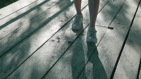 the girl's feet in white sneakers are on white wooden boards Footage