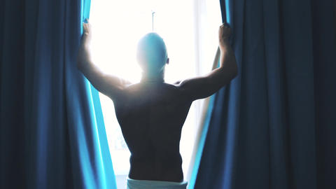 Man opens the curtains in the morning Footage