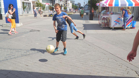 Boys play football on the streets of the city hindering passers-by Footage